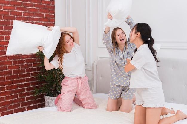 Namoradas brincalhões lutando com travesseiros Foto gratuita