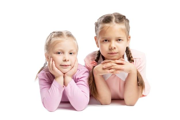 Namoradas em camisolas rosa estão mentindo e sorrindo. crianças pequenas. isolado sobre o fundo branco Foto Premium