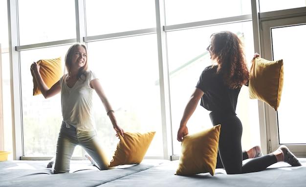 Namoradas engraçadas jogam travesseiros, perto de grandes janelas. Foto gratuita