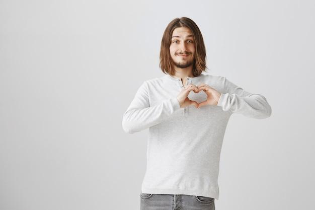 Namorado adorável mostrando um gesto de coração, expressando amor e carinho Foto gratuita
