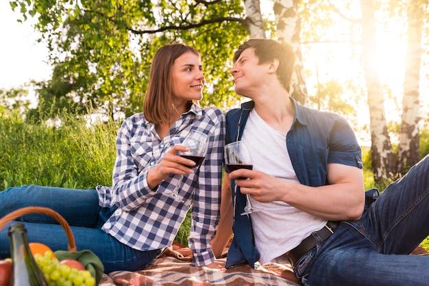 Namorado e namorada bebendo vinho no piquenique Foto gratuita