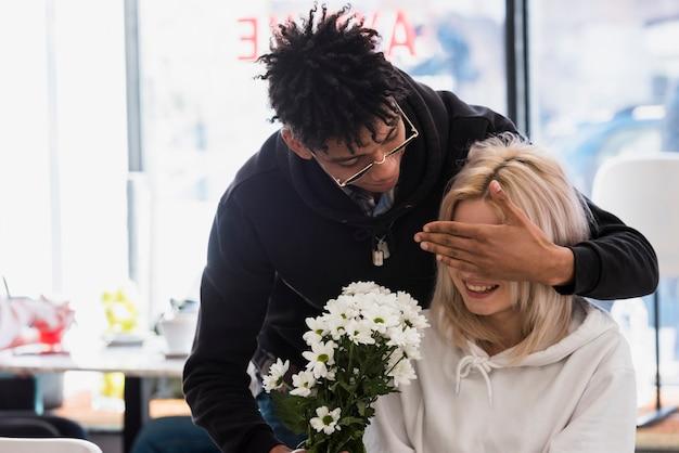 Namorado, escondendo os olhos da namorada, dando o buquê de flores brancas Foto gratuita