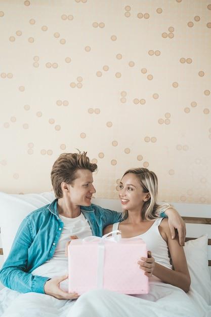 Namorado surpreender sua namorada com caixa de presente na cama Foto gratuita