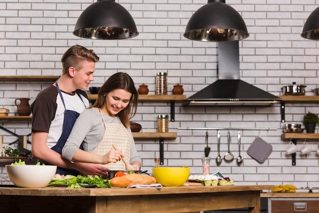 Namorados cozinhar na mesa na cozinha Foto gratuita