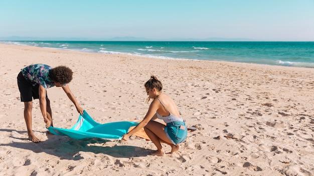 Namorados espalhando toalha na praia Foto gratuita
