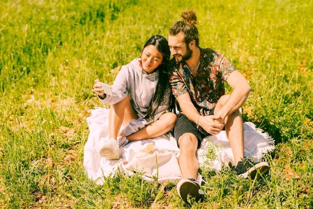 Namorados multiétnicas bonitos, tendo selfie em campo Foto gratuita