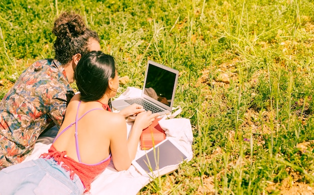 Namorados usando laptop no campo Foto gratuita