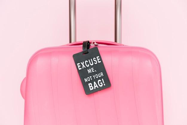 Não é sua etiqueta de saco na mala de viagem rosa contra fundo rosa Foto gratuita