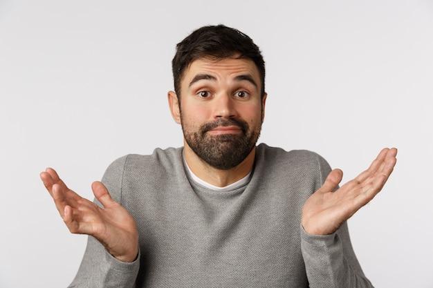 Não estou envolvido, desculpe, não posso ajudar. pai barbudo, jovem, sem noção e sem noção, evite responder a perguntas, encolher os ombros para o lado, sorrir incerto e intrigado Foto Premium