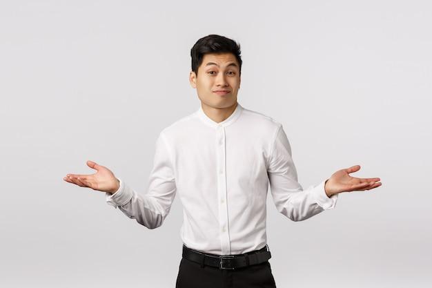 Não posso ajudá-lo a se desculpar. empresário asiático bonito encolher os ombros, espalhar as mãos para o lado consternação e admiração, franzindo a testa e sorrir desajeitado, não sei nada, sem noção, incapaz de responder Foto Premium