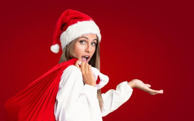 Nas férias de natal jovem mulher loira pegando um saco cheio de presentes ao longo da parede vermelha isolada Foto Premium