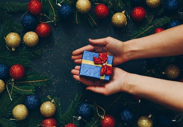 Nas mãos de uma menina segurando um presente de natal em um fundo preto Foto Premium