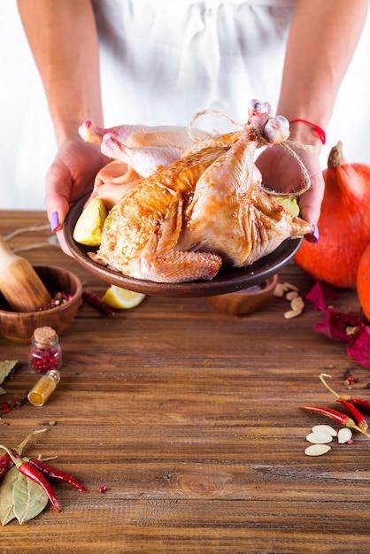 Nas mãos femininas o frango em molho e temperos em um prato Foto Premium