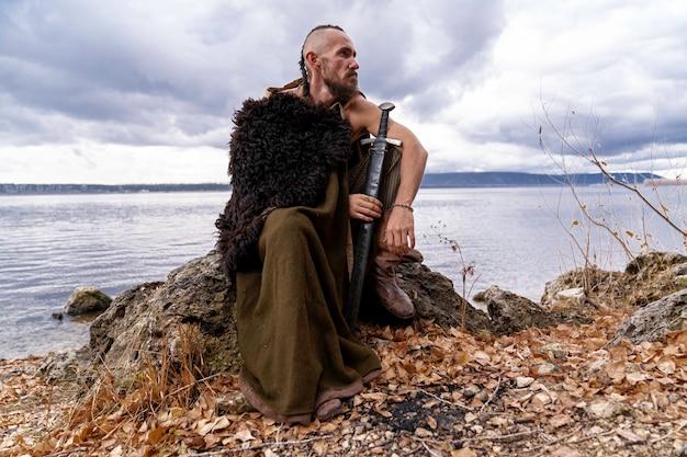 Nas margens do rio, um viking vestido com uma pele de animal está sentado em uma pedra segurando uma espada Foto Premium