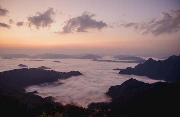Nascer do sol com montanha escura e névoa Foto Premium