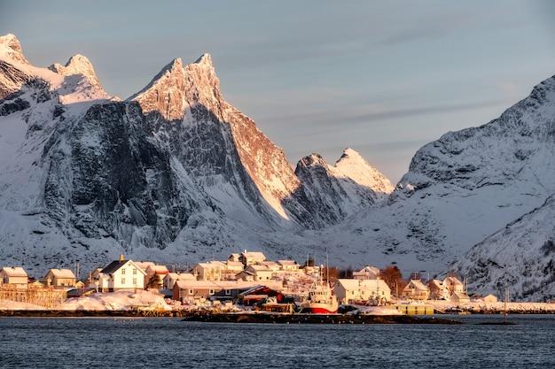 Nascer do sol na aldeia escandinava com fundo de montanha de neve no litoral Foto Premium