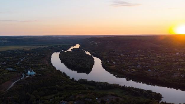 Nascer do sol na moldávia, vila com igreja ortodoxa e rio se dividindo em duas partes Foto gratuita