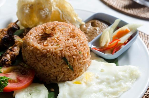 Nasi lemack estilo prato legumes frescos nozes e peixe com arroz popular em toda a indonésia Foto Premium