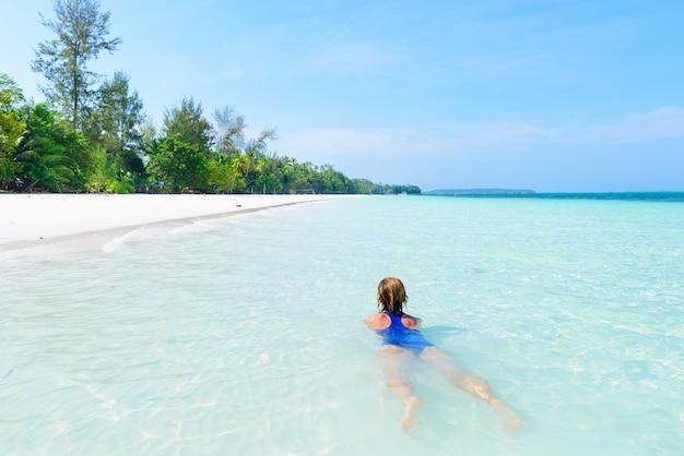 Natação da mulher na água transparente de turquesa do mar das caraíbas. praia tropical nas ilhas molucas de kei, destino do turista do verão em indonésia. Foto Premium