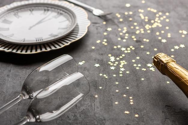 Natal, celebração de ano novo, servindo prato de forma de relógio, garrafas de champanhe, duas taças de champanhe e confetes de glitter dourados, t Foto Premium