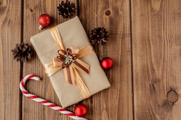 Natal com cones de natal e brinquedos, ramos de abeto, caixas de presente e decorações em uma mesa de madeira Foto Premium