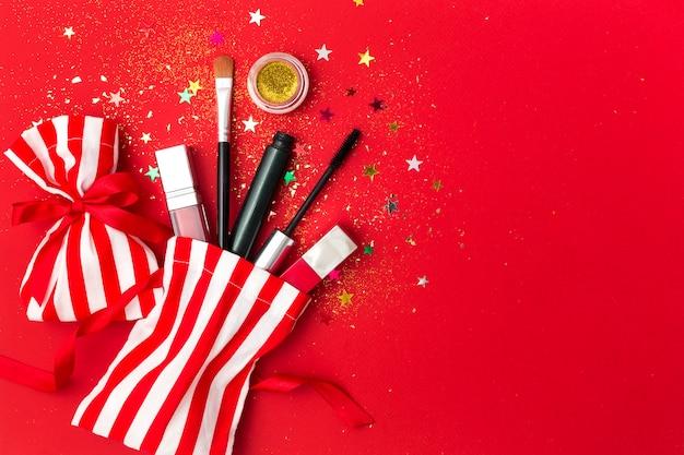 Natal com rímel, batom e sombras. composição plana leiga com brilhos, sacolas de presente e produtos cosméticos para a festa de ano novo. Foto Premium