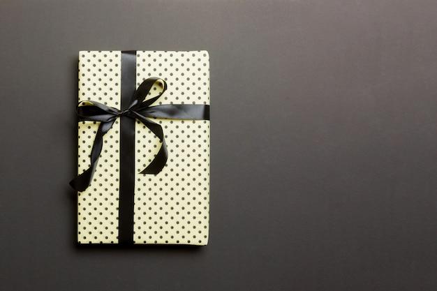 Natal embrulhado ou outro presente artesanal de férias em papel com fita preta sobre fundo preto Foto Premium