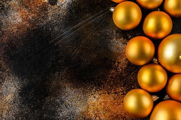 Natal flat lay, fundo de ano novo. enfeites de ouro sobre fundo escuro. Foto Premium
