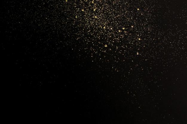 Natal glitter dourados sobre fundo preto. resumo de férias Foto Premium