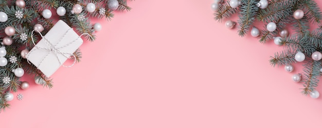 Natal prata rosa vidro bola e abeto ramos rosa. banner de natal. copyspace. vista de cima. Foto Premium