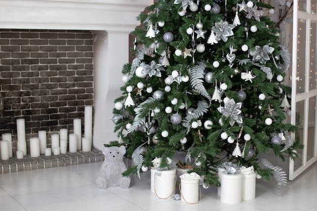 Natal! sala de estar decorada com lareira com linda árvore de natal e bolas. caixas de presente de natal no chão perto de abeto na sala. Foto Premium