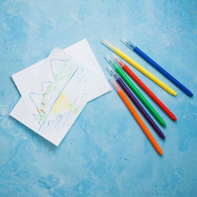 Natureza, desenho na página em branco com caneta de ponta de feltro sobre a superfície azul Foto gratuita