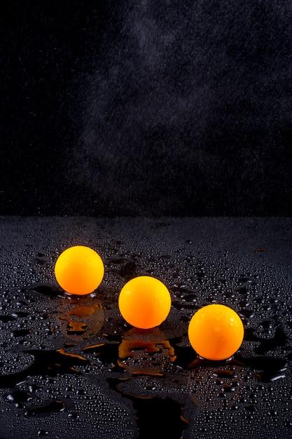 Natureza morta abstrata com três bolas de laranja sob irrigação por gotejamento com água Foto Premium