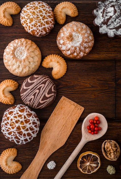 Natureza morta aconchegante com conjunto de padaria: biscoitos caseiros, bolos, nozes, amora na textura de madeira escura. Foto Premium
