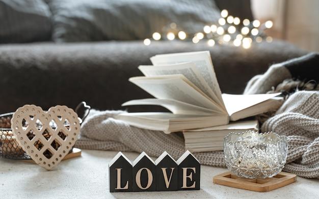 Natureza morta com a palavra de madeira amor, livros e itens aconchegantes em um fundo desfocado com boke. Foto gratuita