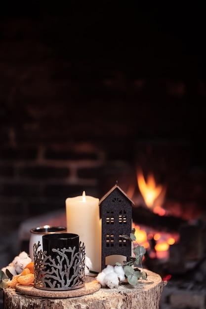 Natureza morta com bebidas quentes, vela e decoração contra fogo aceso. o conceito de um relaxamento noturno perto da lareira. Foto gratuita