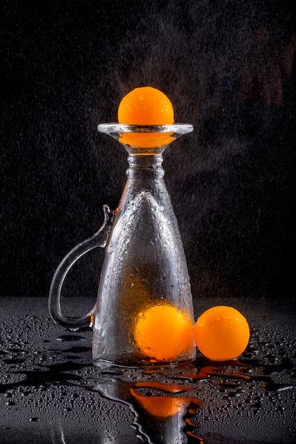 Natureza morta com bolas de laranja e um copo de vidro sob irrigação por gotejamento com água Foto Premium