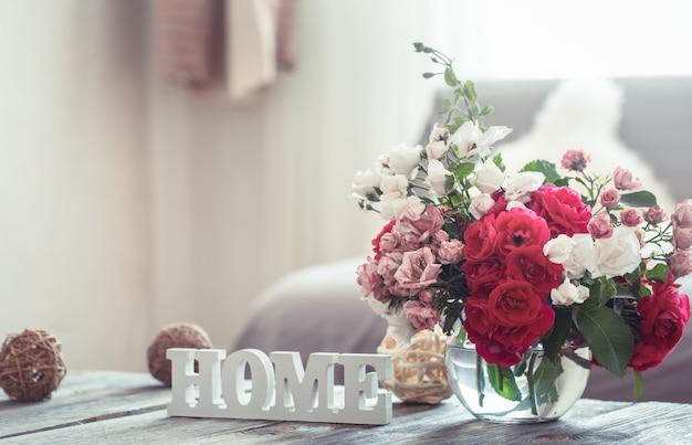 Natureza morta com uma casa de inscrição e um vaso com flores de rosas diferentes. o conceito de conforto e decoração do lar. Foto gratuita