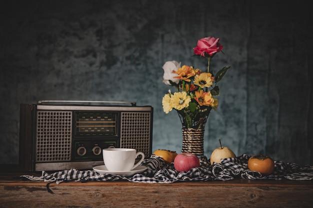 Natureza morta com vasos de flores com frutas e rádio retrô Foto gratuita
