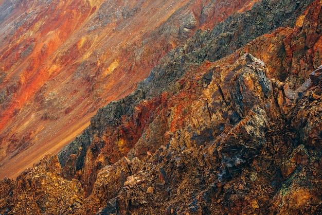 Natureza multicolor vívida da grande montanha rochosa com rochas pontudas. superfície do quadro completo de close-up de parede áspera montanha gigante. pedras vermelhas laranja amarelas. belo cenário natural das montanhas rochosas. Foto Premium