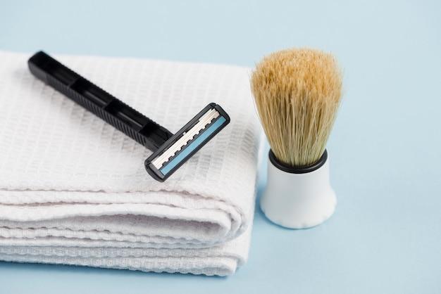Navalha, ligado, branca, dobrado, guardanapo, e, clássicas, escova raspando, contra, experiência azul Foto gratuita