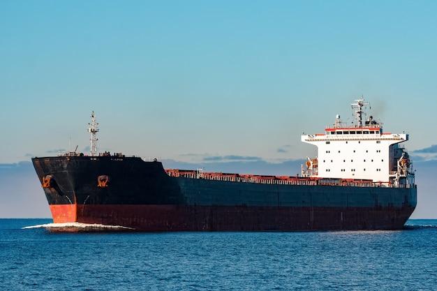 Navio de carga preto em movimento na água do mar báltico. riga, europa Foto Premium