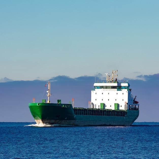 Navio de carga verde movendo-se nas águas paradas do mar báltico Foto Premium