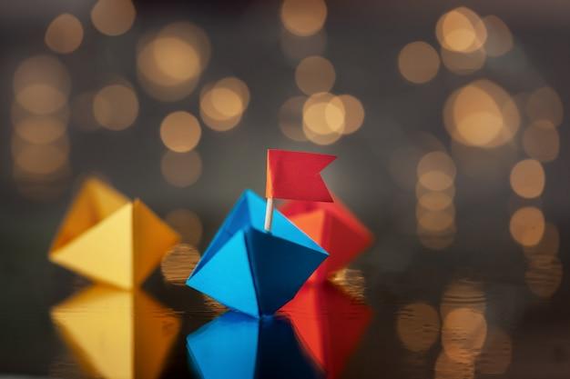 Navio de papel azul com bandeira entre outros navios. Foto Premium