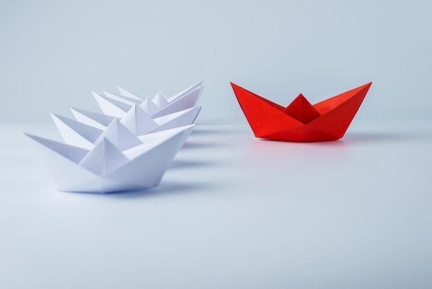 Navio de papel vermelho liderando entre branco Foto Premium