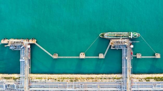 Navio de petroleiro da vista aérea que descarrega no porto, óleo da exportação da importação do negócio com óleo do transporte do navio de petroleiro da refinaria no mar. Foto Premium