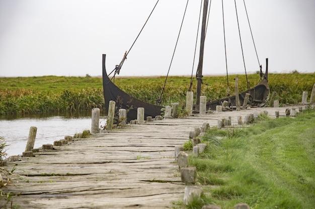 Navio enferrujado no lago perto da doca de madeira em uma vila viking sob o céu claro Foto gratuita