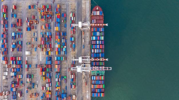 Navio porta-contentores de carga e descarga no porto de alto mar, vista aérea superior de importação e exportação de logística de negócios Foto Premium