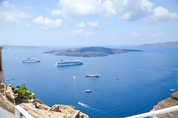 Navios que navegam no mar perto da ilha pitoresca de santorini. Foto Premium
