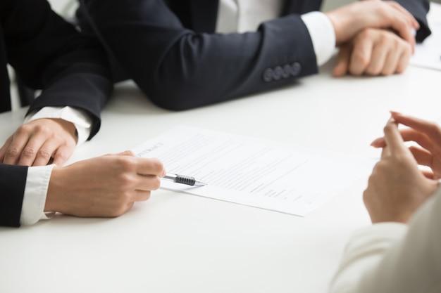 Negociações sobre o conceito de termos do contrato, mão apontando para o documento, closeup Foto gratuita